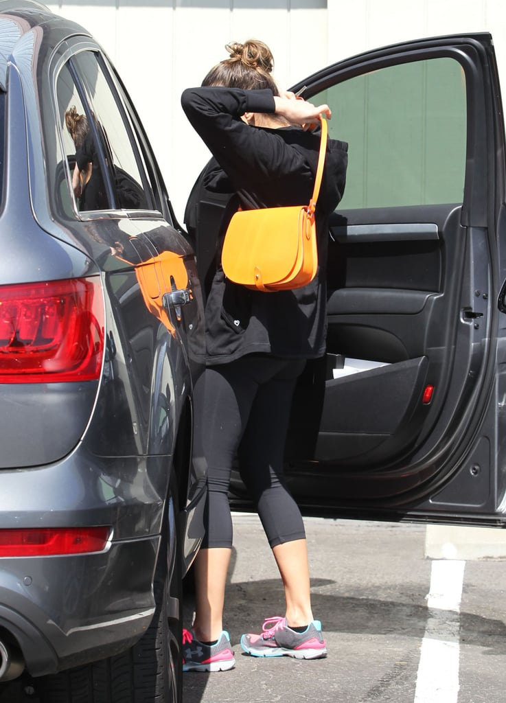 Jessica Alba grabbed her bright orange bag from the car on the way into her office.