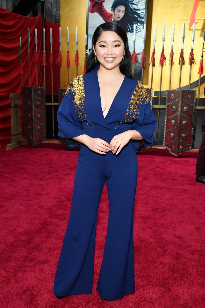 At a red carpet event celebrating one of the fiercest Disney princesses, Lana Condor certainly dressed the part. The To All the Boys I've Loved Before actress recently attended the Los Angeles premiere of the upcoming Mulan remake wearing a regal Antonio Berardi jumpsuit with gold beaded shoulders and elegant kimono sleeves, all somewhat resembling a superhero cape. Styled by Tara Swennen, the outfit was completed with black Tamara Mellon heels, as well as Halleh jewelry and a diamond band by Lark and Berry. Meanwhile, the star of the live-action adaptation, Liu Yifei, wore a voluminous champagne-colored Elie Saab gown that truly made her look like a real-life princess. Marvel at photos of Lana's confident red carpet look ahead.