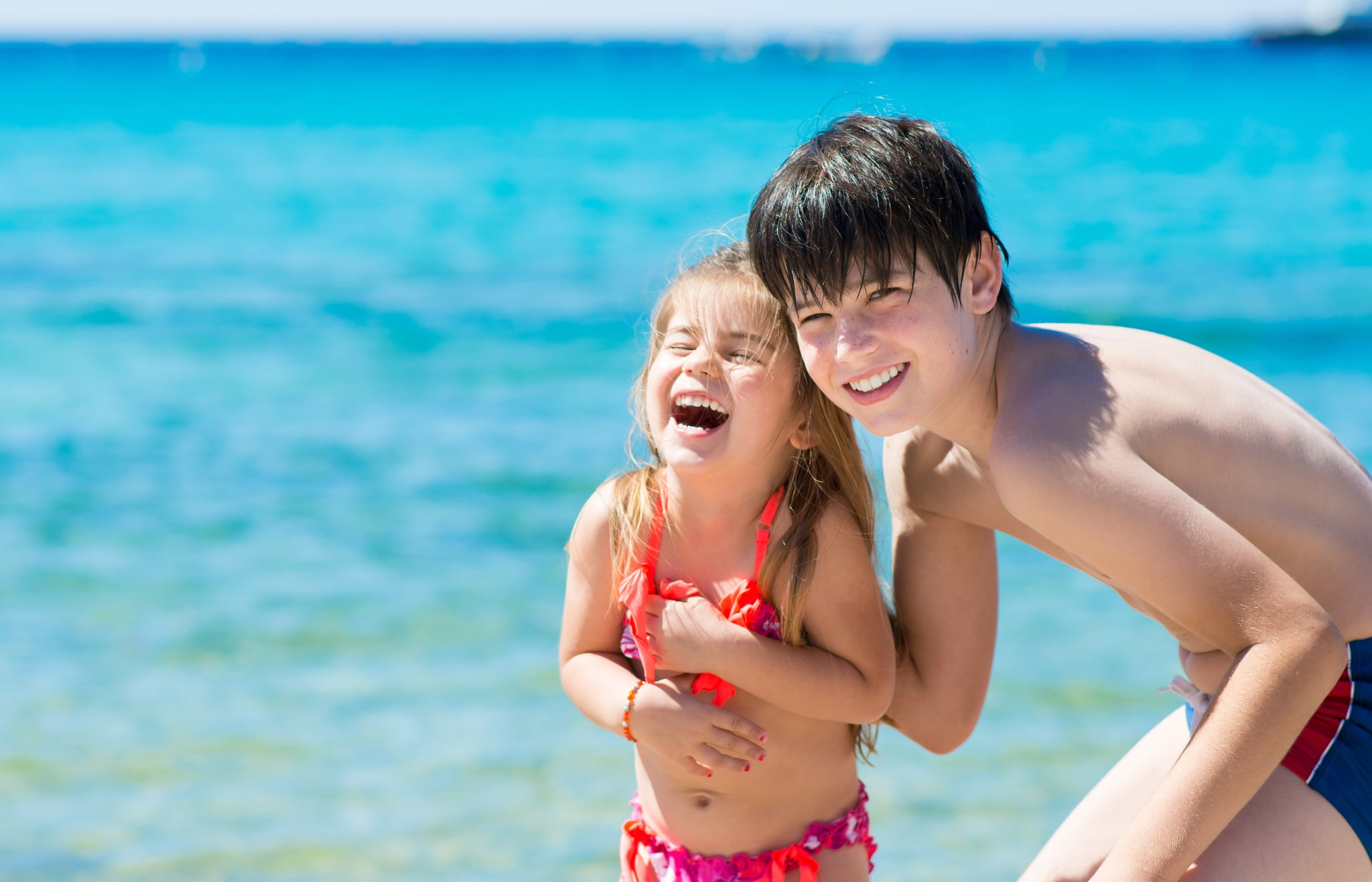 Brother and sister playing on beach vacation, blue sea background