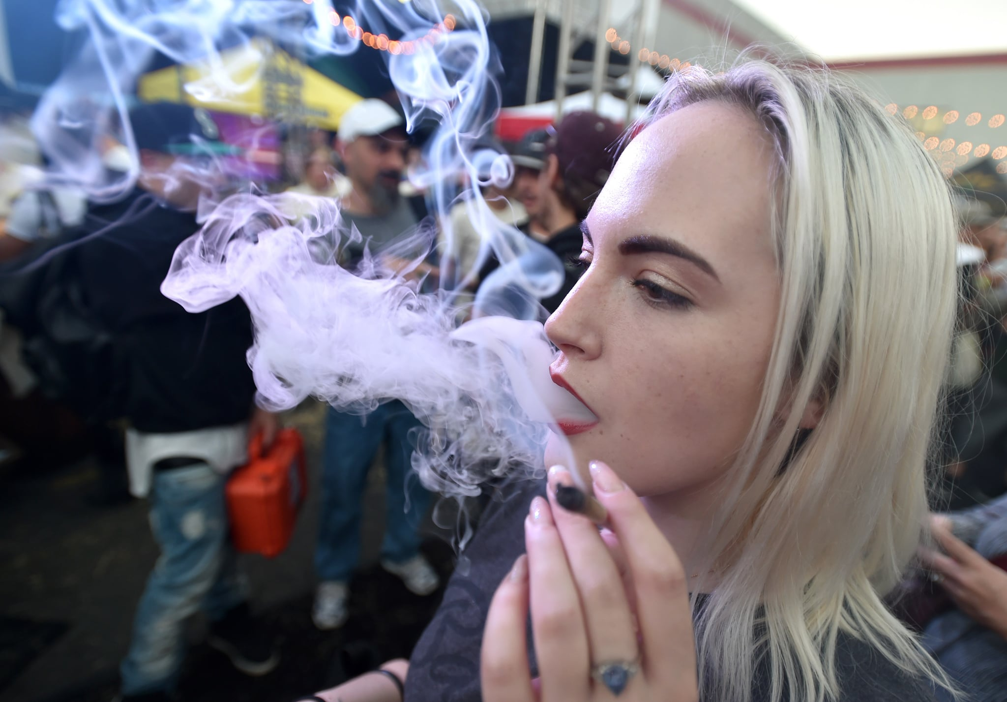 A woman from Seattle, smokes a joint at the first annual DOPE Cup, a cannabis competition in Portland, Oregon, on October 4, 2015. As of October 1, 2015 limited amounts of recreational marijuana became legal for all adults over the age of 21 to purchase in the state of Oregon. AFP PHOTO/JOSH EDELSON        (Photo credit should read Josh Edelson/AFP/Getty Images)