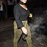 Leaving Prabal Gurung wearing a black keyhole sweater with green suede pants and white boots.