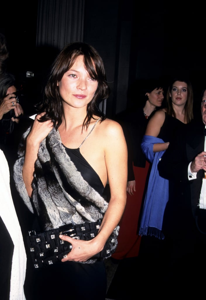 Wearing a black dress and a fur stole to the Met Gala in 1999.
