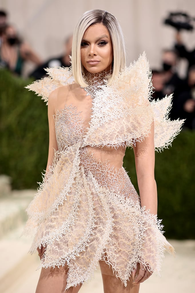 """So, the internet tells me Hailee Steinfeld has arrived at the 2021 Met Gala. I say this even though my own two eyes do not believe it to be true.  The actress — you know, True Grit, Pitch Perfect, Dickinson! — arrived at the esteemed fashion event looking completely unrecognizable. (Yes, the term is overused, but if there were ever a time to use it, the time is now.) In her 10th Met Gala appearance, Steinfeld wore an extraterrestrial Iris van Herpen dress with a bluntly cut blond bob and bleached eyebrows to match her purposefully muted makeup. Her new cut and color were courtesy of hairstylist Ruslan Nureev, a transformation in which he captioned a new Instagram Story, """"Did something different."""" Uh, ya think? See photos of her alleged appearance ahead.      Related:                                                                                                           Whew, These Met Gala Beauty Looks Were Worth the Wait"""
