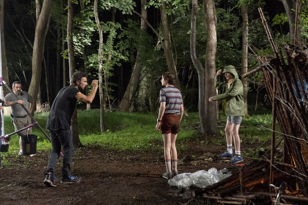 Noah Schnapp and Finn Wolfhard film a tense scene involving their characters in the woods.