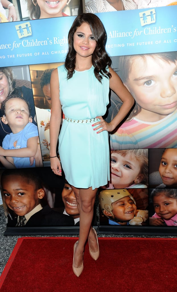 At the Alliance For Children's Rights event in Hollywood, Selena looked youthful in a blue Versace dress with a studded belt from the Spring 2012 collection with nude pumps.