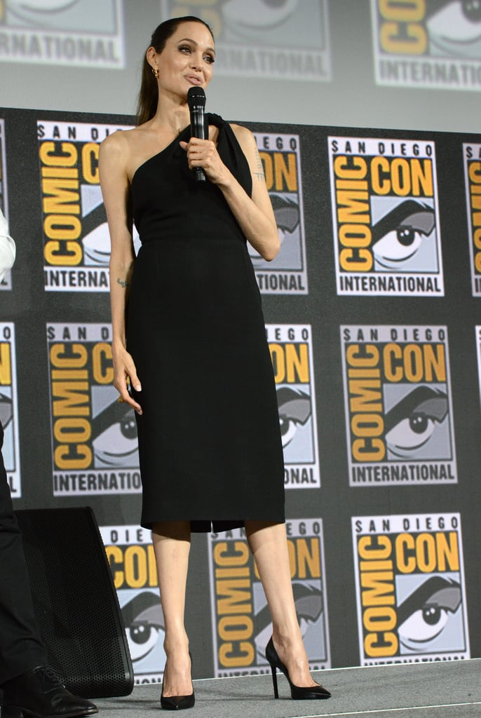 If Angelina Jolie's going to make a surprise appearance, you can bet she's going to do it in style. The 44-year-old actress spent her Saturday night in San Diego to confirm her Eternals role during Marvel's star-studded Comic-Con panel, and stunned the crowd in a classic one-shoulder LBD.  Angelina has acquired quite a few styling hacks over the years, but her fail-safe always seems to be a trusty black dress. For her exciting Comic-Con reveal, she kept things stunningly simple with a longer hemline and subtle knot detailing at the shoulder. She tied the outfit together with pointed black stiletto pumps and gold Cartier jewelry — a perfectly polished pairing. Keep reading to see more photos of Angelina's attire, and catch up on the Summer dress she wore in Paris earlier this month.