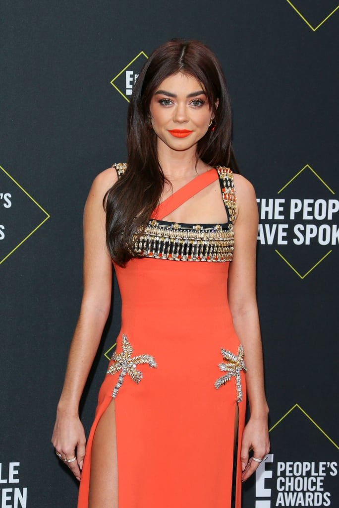 Sarah Hyland knows how to dress for a theme. At the 2019 People's Choice Awards in Santa Monica on Sunday, the actress and Modern Family star wore a coral-orange Fausto Puglisi dress fitting for the award show's sunny setting.  The floor-length dress, from the brand's Spring 2019 ready-to-wear collection, features an embellished, asymmetrical neckline and two thigh-high slits with crystal palm trees atop them. Stylist Brad Goreski then completed Sarah's look with strappy stiletto sandals and a few extra diamond rings in addition, of course, to her oval-shaped engagement ring. See pictures of Sarah's vibrant red carpet look ahead.