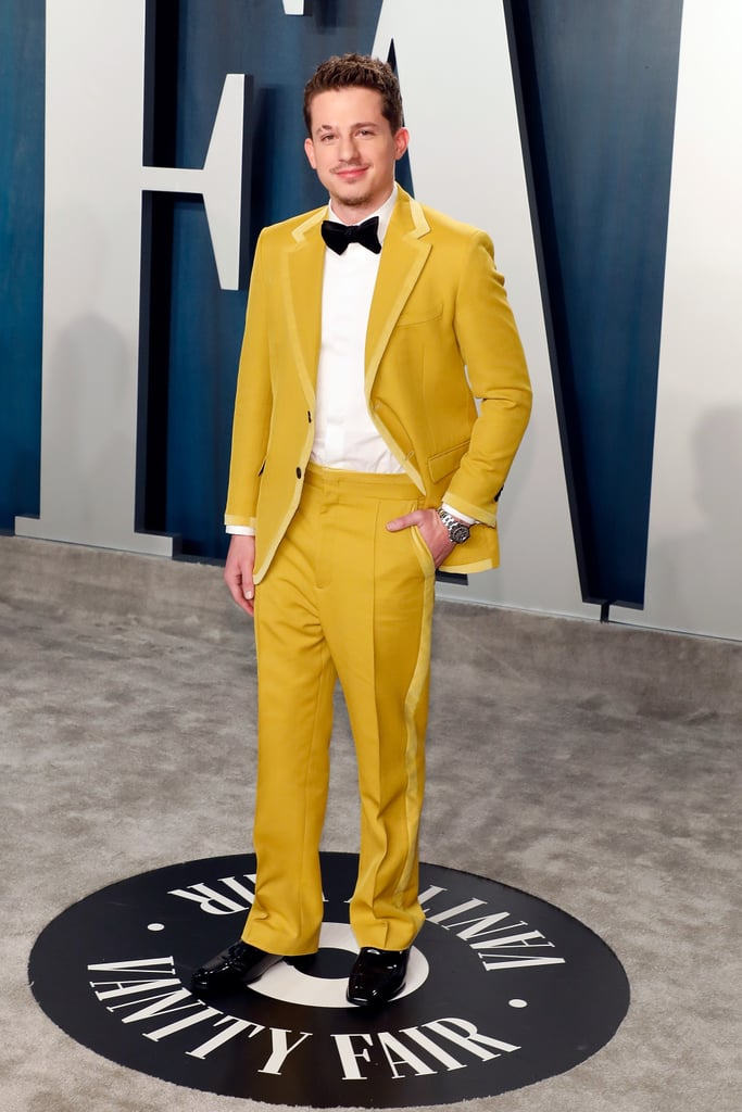 """Charlie Puth and Tyler the Creator must be on the same 2020 fashion wavelength, because the bright yellow Fendi suit the singer wore to the 2020 Vanity Fair Oscars afterparty is straight out of Wes Anderson's closet. Charlie's suit featured a classic cut and thick yellow accent stripes along the sides of the pants, and his eye-catching outfit would make him the best-dressed bellhop at the Grand Budapest Hotel, if you ask me.  The """"Mother"""" singer accessorised with slick black dress shoes, a silver watch, and a traditional black bow tie to pull the whole look together. There's no telling whether Charlie had just made his way back from the Moonrise Kingdom or the Isle of Dogs, but he definitely made this classy look work from every angle. So, in the words of Monsieur Gustave, """"Keep your hands off my lobby boy!"""" and take a closer look at Charlie's yellow suit ahead.      Related:                                                                                                           Zoey Deutch Served Up Little Blue Riding Hood Realness With Her Oscars After Party Dress"""