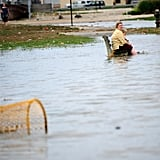 A woman and child sit on a bench in the flooded street near Rockway Beach, NY.