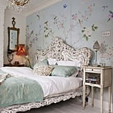 This bedroom is overtly feminine with an ornate bed frame, Victorian lampshade, and hand-painted floral wall mural. The soft palette is especially charming. Source
