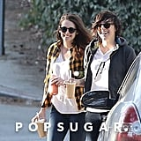 Kristen and her friend laughed while carrying drinks.
