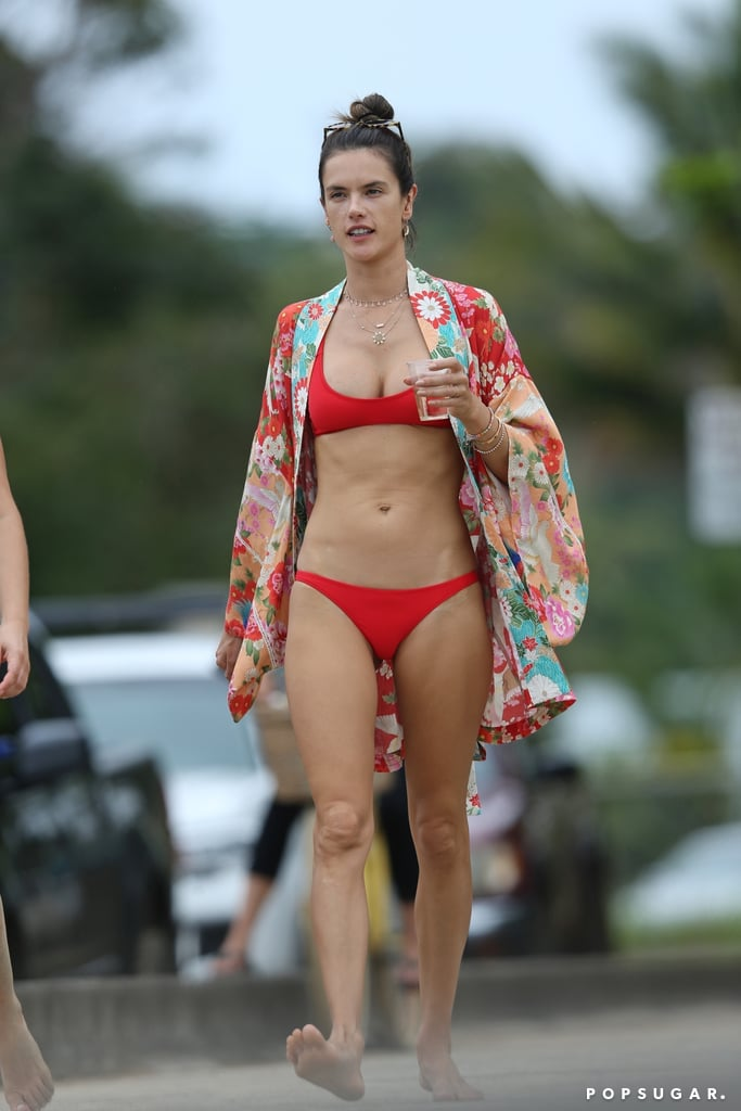 Like her Instagram hashtag says, Alessandra Ambrosio is #foreveronvacation. The model has worn swimsuit after swimsuit while in Hawaii and showed no signs of stopping anytime soon. While taking a stroll on the beach, Alessandra rocked a red two-piece. Though the hue was similar to her past one-piece and bandeau bikini, the scoop design made this particular swimsuit feel completely new. It helped that she also chose a gorgeous breezy floral cover-up to complete her beach attire. The red prints matched perfectly with her tiny bikini. Read on to see her full look, then shop similar pieces for your own holiday.