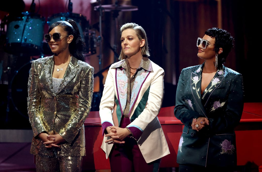 """Demi Lovato, Brandi Carlile, and H.E.R. paid tribute to Elton John during Thursday night's iHeartRadio Music Awards, and the legendary singer himself imparted a few words of wisdom prior to the performance. """"Relax, I'm so glad and appreciative that they're doing it,"""" John said in a pre-show interview with Elvis Duran. After all, they were each handpicked by John for the performance. H.E.R. kicked things off playing piano and guitar for """"Bennie and the Jets,"""" even getting a reaction out of John, who could be seen yelling, """"YES!"""" Carlile then mellowed things out with fan-favorite """"Don't Let the Sun Go Down on Me."""" Finally, Lovato gave it their all, and got John to join in for """"I'm Still Standing."""" Coldplay's Chris Martin introduced the medley in a purposefully chaotic speech about John and his well-known songs, namely """"Uptown Girl"""" and """"I Just Called to Say I Love You."""" (In case you're wondering, that was a joke """"made"""" by the teleprompter operator since Billy Joel sang """"Uptown Girl"""" and Stevie Wonder sang """"I Just Called to Say I Love You."""") Following the performance, Lil Nas X also honored John, describing him as a """"trailblazer to those who live their lives freely and unapologetically."""" John returned the compliment in his acceptance speech, saying, """"A special thanks to Lil Nas X, because he is a wonderful artist and has balls of steel!""""  You can see highlights from the tribute performance and John's speech ahead.      Related:                                                                                                           Demi Lovato Debuted an Edgy Mullet Haircut at the iHeartRadio Awards, and We're Obsessed"""