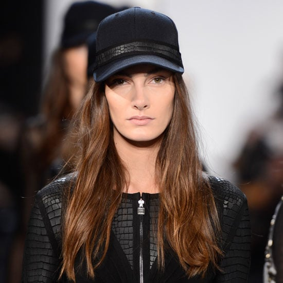 Hervé Léger by Max Azria sent bronzed beauties down the catwalk, a move that directly contrasted with usual Fall 2013 palettes. The hair was windblown in order to emulate the style of a motorcycle-riding tough-girl, while the contoured makeup also fell in line with his California-cool vibe. The look: Finger-styled strands (under hats), beach-bunny tans, and nearly black nails. The inspiration: LA biker girls.  Who would wear it: The woman who counts chains and studs in her fashion repertoire.