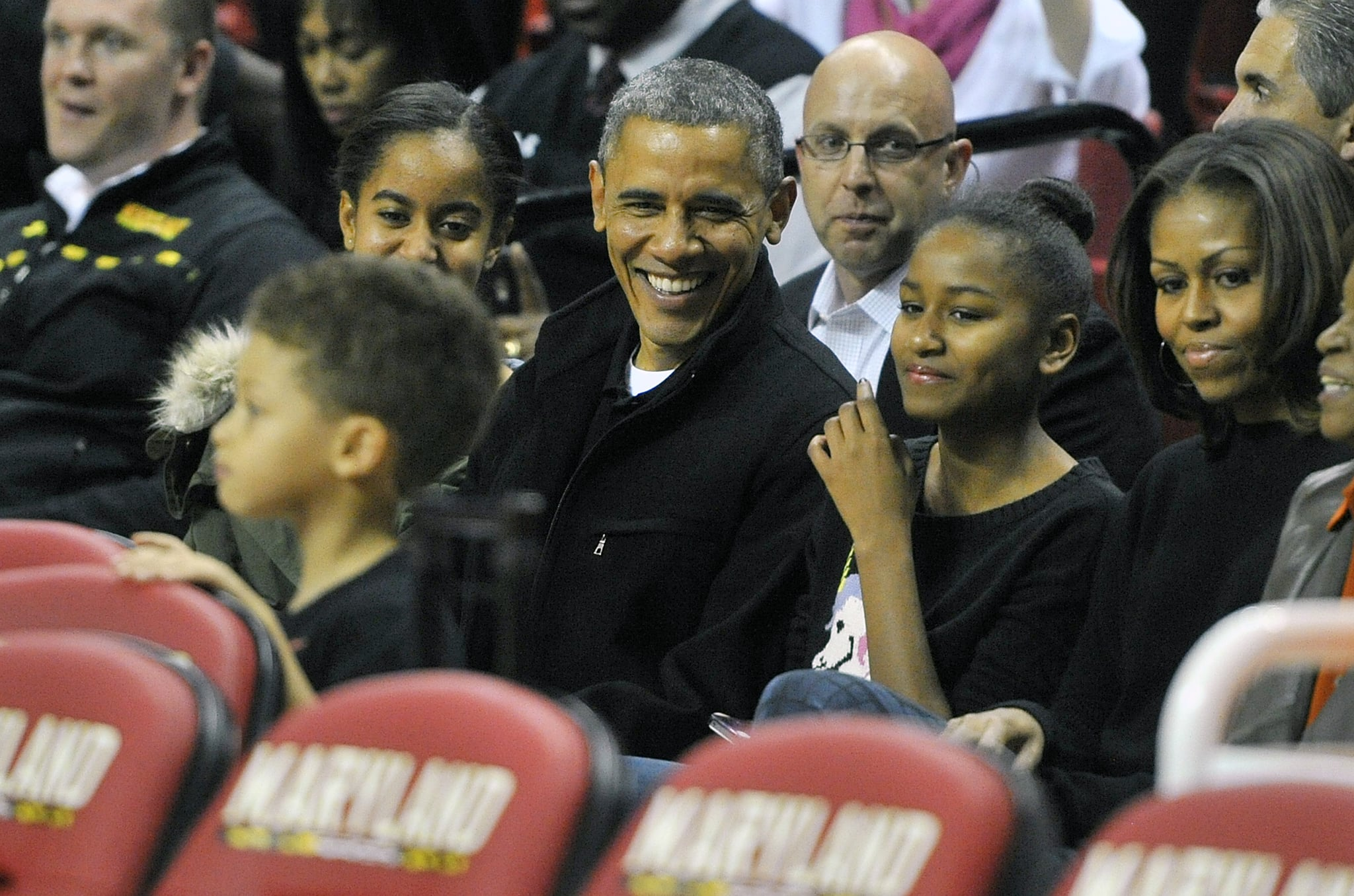 COLLEGE PARK, MD - NOVEMBER 17: President of the United States Barack Obama with his daughters Malia (L) and Sasha (R) and wife Michelle in their seats before a college basketball game between the Oregon State Beavers and the Maryland Terrapins at the Comcast Center on November 17, 2013 in College Park, Maryland.(Photo by G Fiume/Maryland Terrapins/Getty Images)