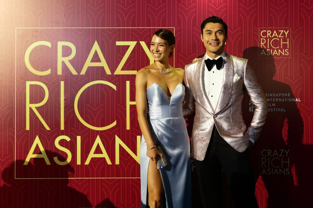 Henry Golding and his wife, Liv Lo, are crazy adorable together, and their latest appearance is solid proof! After attending the world premiere of Crazy Rich Asians in LA earlier this month, the couple jetted to their hometown Singapore for the film's premiere on Monday night. In addition to showing off their sweet love as they held hands on the blue carpet, the two looked absolutely breathtaking as they posed for the cameras. While Henry wore a flashy jacket, his wife stunned in a strapless blue dress. Is it just us, or do these two look like a modern-day Prince Charming and Cinderella? See more of their gorgeous date night ahead.