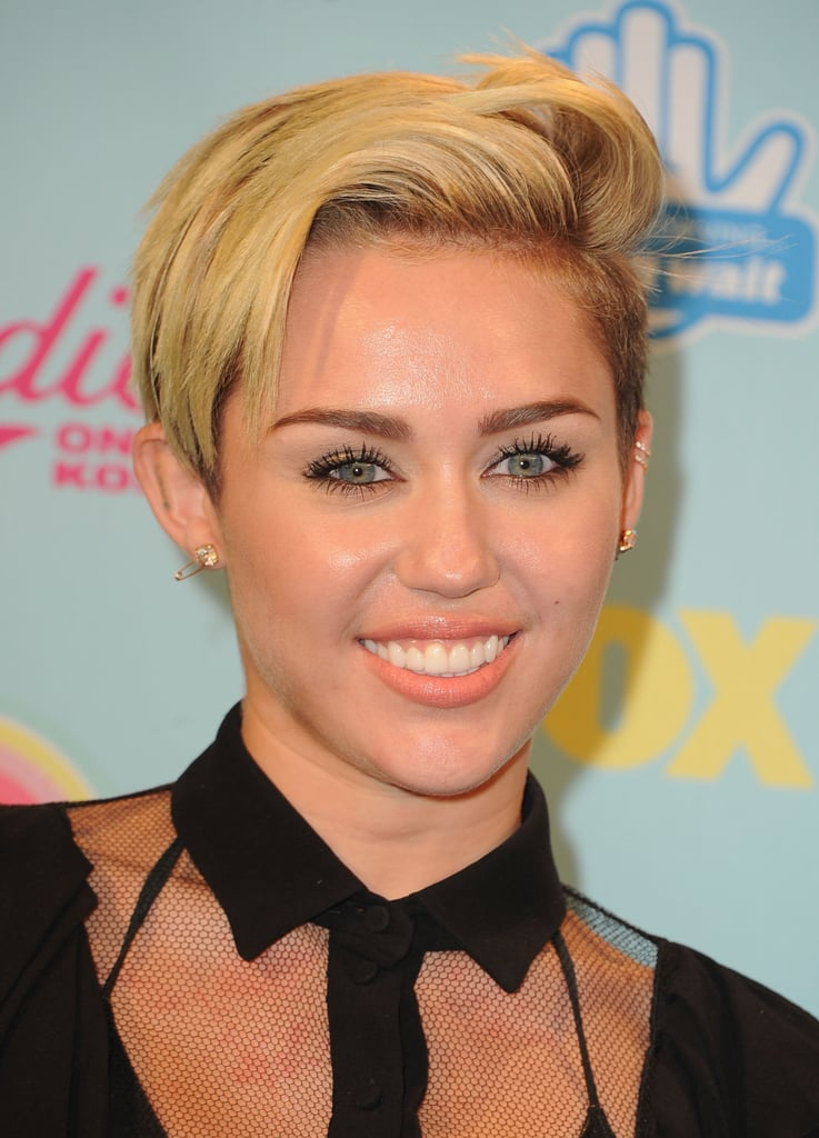 Miley Cyrus styled her signature coif in a sideswept style. Bold brows, loads of liner, and a pop of peach on her lips tied the look together.
