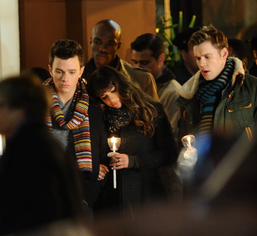 "Lea Michele, Chris Colfer, and Darren Criss joined their Glee castmates to film an emotional candlelight vigil scene in LA on Tuesday. Lea, Chris, and Chord Overstreet sang on a sidewalk while holding small candles. Earlier in the day, Chris and Darren filmed a daytime scene on the same sidewalk, with an injured-looking Chris placing a white flower on a makeshift memorial that featured rainbow flags and ""Get Well"" balloons. The scene was most likely not for the late Cory Monteith's character, Finn, as the LGBT-friendly flags hint that it was possibly for a gay character, like Adam Lambert's Elliot.  The cast's memorial came the same day that Glee returned with new episodes on Fox. (Spoiler alert: Rachel slapped Santana.) The group is currently preparing for their highly anticipated 100th episode, which will air on March 18."