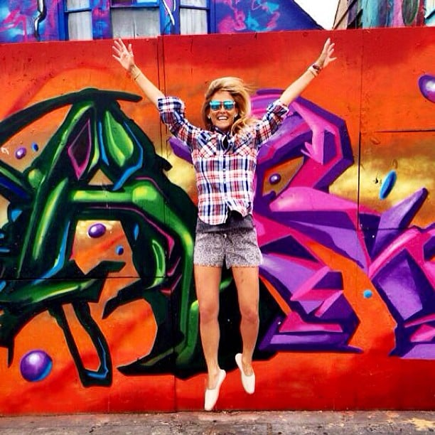 Bar Refaeli took a leap in front of some street art. Source: Instagram user barrefaeli