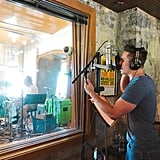 """Justin Adams singing in the """"stone room,"""" which looks into the studio A tracking room."""