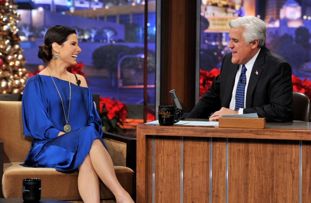 """Sandra Bullock wore a loose blue dress yesterday to sit down for a chat with Jay Leno on The Tonight Show With Jay Leno. The actress was out and about chatting up her upcoming film Extremely Loud and Incredibly Close, which she promoted last week in NYC. While in the Big Apple, Sandra spoke about how she's prepping for her second Christmas with her young son Louis. She plans to spoil him with plenty of presents and even laughed with Today's Matt Lauer about getting Louis a G-V jet!  Last night, Sandra Bullock's Christmas traditions were also up for discussion. She revealed one meal that she and her German relatives just have to have even though it's technically illegal! She said, """"Since my mother passed, we break the law, because we have to manage to smuggle German sausages into the country, and apparently bringing meats across the waters is against the law . . . You fry 'em up with some sauerkraut and potato salad, but they have to be the right ones."""""""