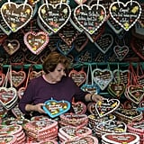 A woman arranges a whole lot of gingerbread hearts at her booth.