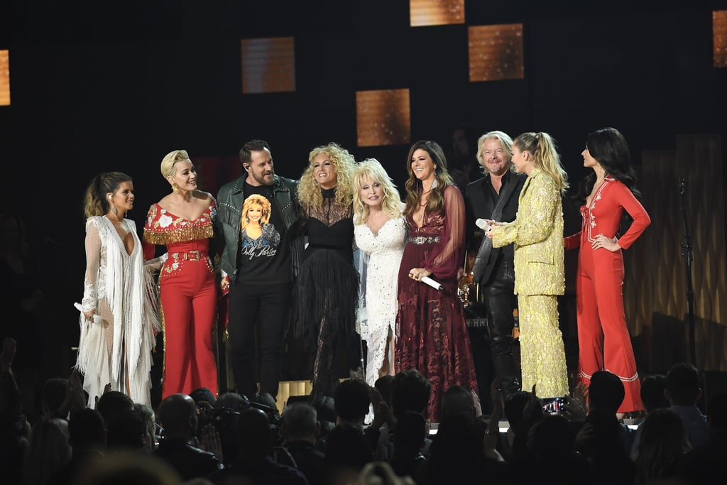 """Here she comes again: after receiving an astounding 47 Grammy Award nominations — and winning eight — Dolly Parton was honored with a tribute at the forthcoming award show on Feb. 10. Miley Cyrus, Kacey Musgraves, Katy Perry, Maren Morris, and Little Big Town performed various songs alongside Parton, including """"Jolene,"""" """"Here She Comes,"""" and more. In addition to the tribute, Parton was also recognized as the 2019 MusiCares Person of the Year. The annual award given out by The Recording Academy's charity honors musicians for philanthropy. Parton has created several charities since launching her Dollywood Foundation in 1986, including Dolly Parton's Imagination Library, which provides books to children, and the My People Fund, which benefited those affected by the Great Smoky Mountains wildfires in 2016.  This marked Parton's first Grammys performance since 2001, when she performed """"Travelin' Prayer."""" She also took home the award for best bluegrass album that year for The Grass Is Blue. While the aforementioned artists delivered a stellar tribute, we truthfully enjoyed seeing the leading lady of country show them how it's done.      Related:                                                                                                           Dolly Parton Brought the Dancing Emoji to Life For Her Huge Night at the Grammys"""