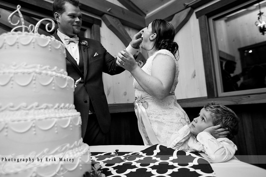 He watched with bated breath as the bride and groom wasted precious bites of cake all over each other's faces in a seemingly ridiculous adult ritual. Get it in your mouth, that's good cake!