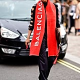 Wear a Logo-Covered Scarf With a Black Ensemble