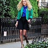 Carrie's flirty black skirt and sensible patent pumps balanced her blue printed tie-neck blouse, kelly green blazer, and bold statement necklace, while her neon-print monogrammed bag added the perfect  touch of pizzazz.