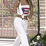 Wearing jeans with suspenders, metallic boots, and an American flag tube top in LA in 2001.