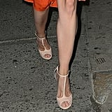 Her nude-toned T-strap sandals provided a cool complement to the bold hue on top.