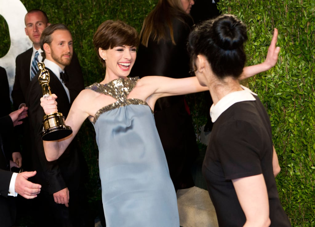 Anne Hathaway couldn't contain her excitement at the Vanity Fair Oscars after party as she greeted Sarah Silverman.