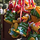 You can find popcorn buckets with Pluto in a Christmas sweater all around Disneyland park.