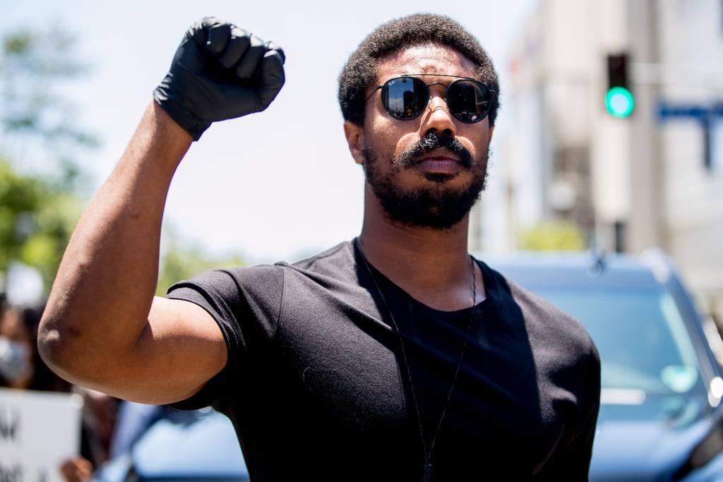 "Michael B. Jordan is calling on Hollywood to be a part of social progress. On Saturday, the 33-year-old actor attended a Black Lives Matter march in LA where he delivered an impassioned speech about thorough diversity in the entertainment industry. He shared how his roles in the films Fruitvale Station, Fahrenheit 451, Black Panther, and Just Mercy made a huge impact on him and his fight for equality.  Michael also opened up about his production company, Outlier Society, and its efforts to enact the ""inclusion rider"" policy, which enforces diverse hiring practices. ""We're in the heart of Hollywood right now — one of the world's most powerful industries, and I'm an active member of that,"" he said. ""They need to go on notice. I dedicated my production company to an inclusion rider, but it has to go beyond that."" He then directly addressed businesses that he's connected to, saying, ""All my brands, anybody that deals with me, if you have racist beliefs, if you have a racist bone in your body, if you're not with me, if you don't stand with me and people that look like me, then you don't need to be with me, and that's point-blank period.""  The actor additionally shared his suport for defunding the police and reallocating financies to causes that benefit all people. ""I want us to invest in Black staff,"" he said. ""I'm proud to have an inclusion rider and all that good stuff, and I use my power to demand diversity, but it's time that studios and agencies — all the agencies, all these buildings that we're standing in front of, I wish you'd do the same. You committed to a 50/50 gender parity in 2020 — where is the challenge to commit to Black hiring, Black content led by Black executives, Black consultants? Are you policing our storytelling as well?""  He ended by encouraging everyone to vote and continue making their voices heard. ""I just want to be here, be present, and show you guys that I'm here with you,"" he said. ""So, let's keep this sh*t going."" Read Michael's full speech below, then keep scrolling to see more powerful photos from the march.  We can't be quiet. I played four very, very important characters that affected my life. Oscar Grant was one of them. Oscar Grant was killed by police on the BART train station in Oakland. I had the opportunity to embody who he was. I got an opportunity to feel the pain of his family — his daughter, his mother — I lived with that for a really long time. It weighs on you. I also played a fireman in Farenheit 451, who was thirsting for knowledge. He joined a revolution. The producer of that movie made me really realize the lengths that the government and oppressors will go to keep knowledge out of your hands. They know that if we unlock this up here, that we'll be unstoppable, and they're scared of that.  Black Panther, Killmonger — he was an activist, a revolutionary. He's the product of a village that does not accept that child, cast him out. He will burn that village to the ground . . . I also had the opportunity and the honor to play Bryan Stevenson. He dedicated his life to combating the racial legal system that we have right now, and, in doing so, I learned. I learned his tactics, I learned his mentality, I learned his approach to things — very calm, very strategic, very thoughtful.  We have to be approximate. We have to be close to issues. That's why I love to support everybody that's out here because we have to be here together, shoulder to shoulder. We're in the heart of Hollywood right now — one of the world's most powerful industries, and I'm an active member of that. They need to go on notice. I dedicated my production company to an inclusion rider, but it has to go beyond that.  So, to the brands that support me, to all the productions, to the studios, to all the businesses and partnerships that I have, if you have any financial ties to police, we have to relook at our business. We have to stop hiring police. We have to cut off their support. That's why I'm committed to hiring private security at all my events — private security only. All my brands, anybody that deals with me, if you have racist beliefs, if you have a racist bone in your body, if you're not with me, if you don't stand with me and people that look like me, then you don't need to be with me, and that's point-blank period.  So I got a few things that I really want to get. So, invest, right? I want us to invest in Black staff, I'm proud to have an inclusion rider and all that good stuff, and I use my power to demand diversity, but it's time that studios and agencies — all the agencies, all these buildings that we're standing in front of, I wish you'd do the same. You committed to a 50/50 gender parity in 2020 — where is the challenge to commit to Black hiring, Black content led by Black executives, Black consultants? Are you policing our storytelling as well?  So let us bring our darkness to the light — Black culture, the sneakers, sports, comedic culture that you guys love so much. We've dealt with discrimination at every turn. Can you help fund Black brands, companies, cultural leaders, Black organizations? A great agent doesn't have to be a great organizer, but a great agent could advocate for relationships with organizers. Will you support nonprofits as working to solve problems of our industry that our industry created?  And you gotta vote. Everybody says it. It's a very easy thing to do. I hear it, I respect it, but voting has never been more important than it is today . . . We can't vote today, but what we're doing today will make our voices heard and values heard. We've got to keep doing it, we've got to keep agitating things, we can't be complacent, we can't let this moment just pass us by. We have to continue to put our foot on their necks. And just know that we are with you guys. I ain't up here for all the extra stuff, man. I just want to be here, be present, and show you guys that I'm here with you. So, let's keep this sh*t going."