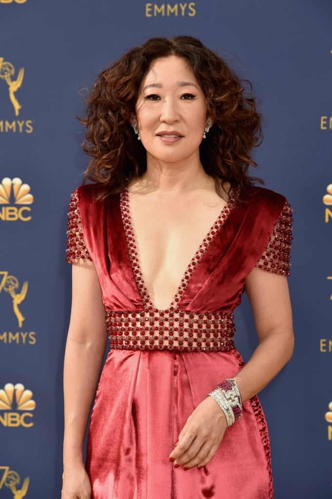 Whatever you're doing, you need to stop and sit down so you can properly appreciate just how wonderful Sandra Oh's appearance at the Emmys was on Monday night. Yes, she looked glamorous as ever — that plunging red dress? YES, Sandra! — but it was the fact that she brought along her parents, Mr. and Mrs. Oh, as her dates that really made our hearts explode.  The Killing Eve actress made history this year with her outstanding lead actress in a drama nomination for the brilliant BBC spy thriller, becoming the first Asian actor to be nominated in the category. Luckily she had her family's support as she hit the red carpet in a dress sexy enough to stop traffic (AND international female assassins) (probably).  The Grey's Anatomy alum also introduced her mom to This Is Us star Milo Ventimiglia and later posed with his costar Chrissy Metz on the red carpet, all of which was just as cute as it sounds. See more adorable moments from Sandra's night out at the 70th annual Emmys ahead!