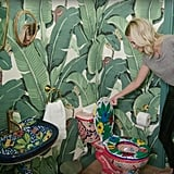 This guest bathroom features bold tropical wallpaper and an adorable patterned toilet they bought on eBay.