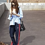 Dress up tracksuit bottoms with a button-down shirt, then let it hang off your shoulders for the full fashion-girl effect.