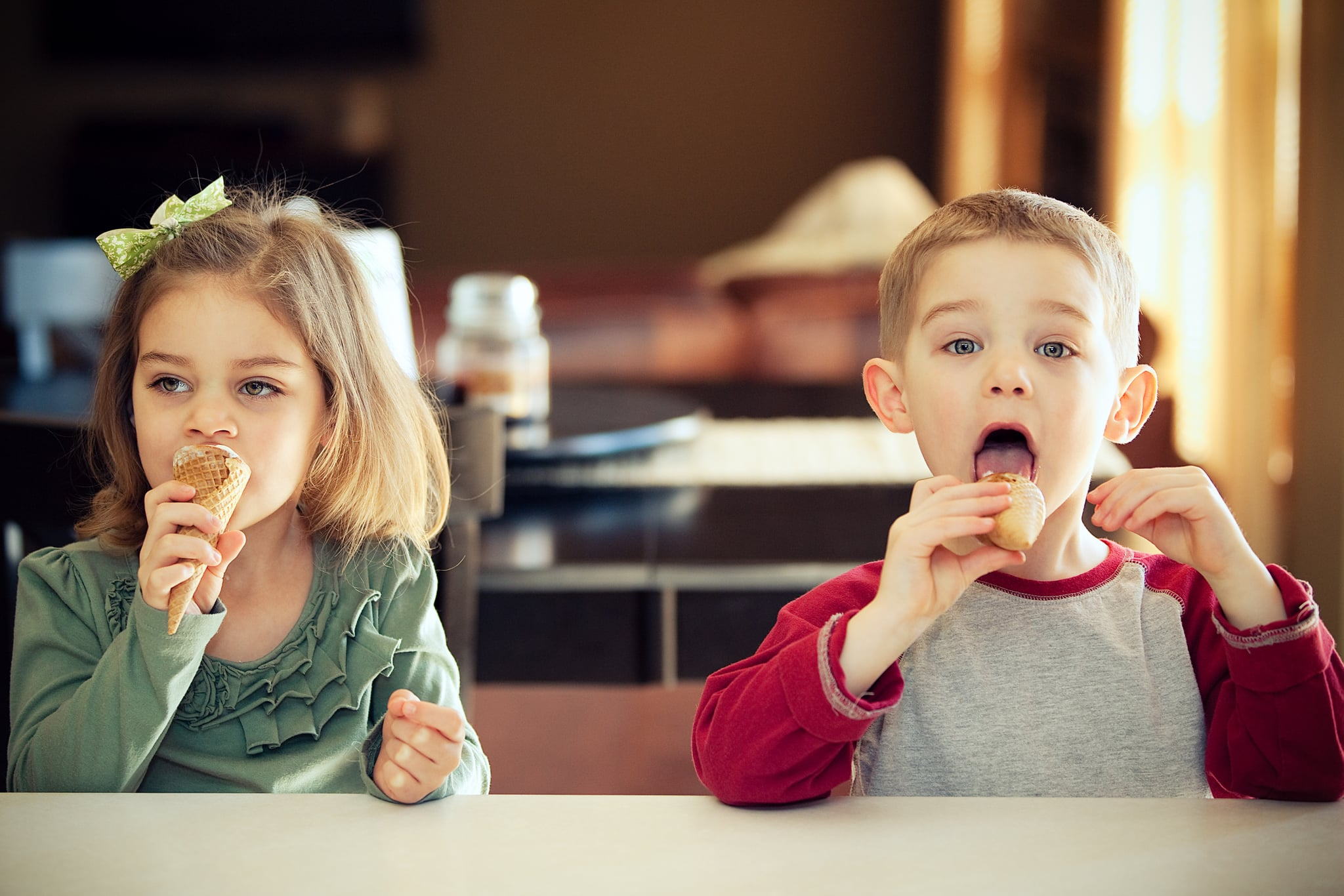 Boy and girl twins at home seated at counter in their kitchen eating ice cream cones, boy is caught wide eyed mid lick.