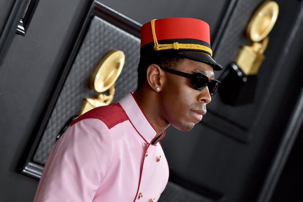 "Checking in? Tyler the Creator arrived at the 2020 Grammy Awards on Sunday wearing a pink and red bellhop suit that looked plucked right out of Wes Anderson's cinematic universe. The alternative rapper and music industry class clown completed the Golf le Fleur look with a matching hat, white oxfords, gloves, square sunglasses, and a suitcase filled with clothing — perhaps his performance outfit? — including a striped shirt and a massive chain necklace with a pendant inspired by Tyler's look in the ""Earfquake"" music video. See photos of his rule-breaking red carpet outfit ahead, and then see what everyone else wore to the award show.      Related:                                                                                                           Billie Eilish's Grammys Outfit Is the Gucci Equivalent of Camouflage"