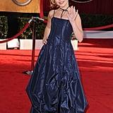 Wearing a blue satin dress.