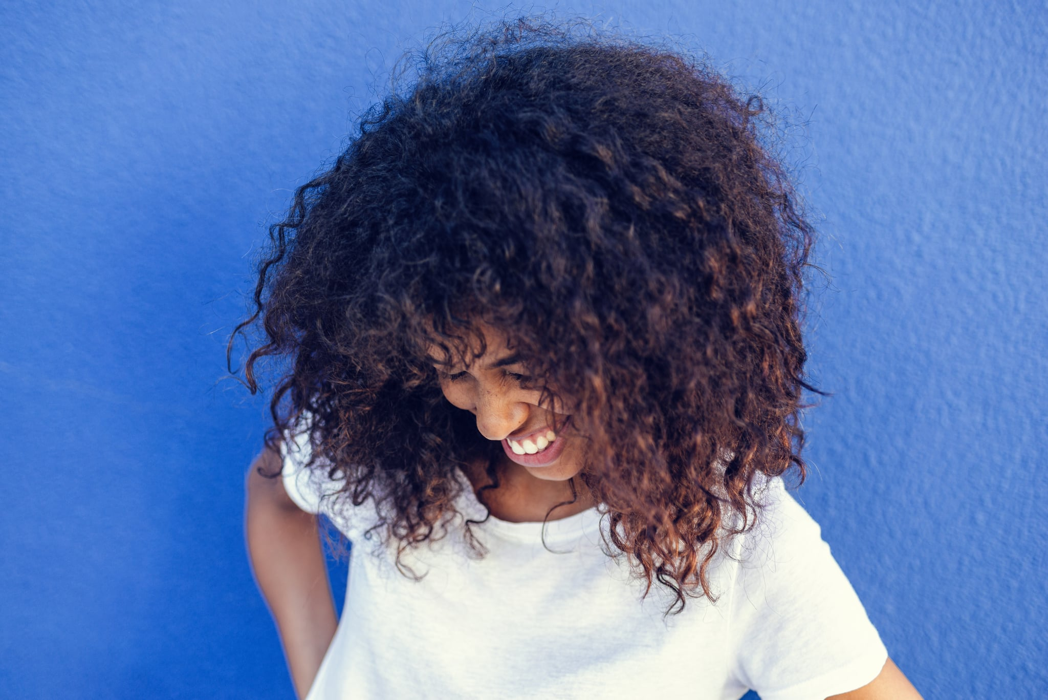 Portrait of smiling woman with blue background