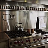 The kitchen features stainless steel appliances throughout (and check out that beautifully organized spice shelf!).