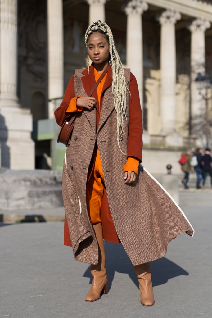 A Bright Orange Jumpsuit, Rust Coat, Brown Sleeveless Jacket, and Boots