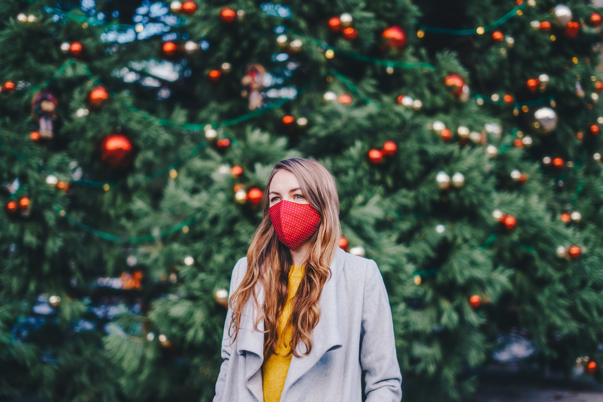 Woman wearing a fabric face mask outdoors in front of the Christmas tree