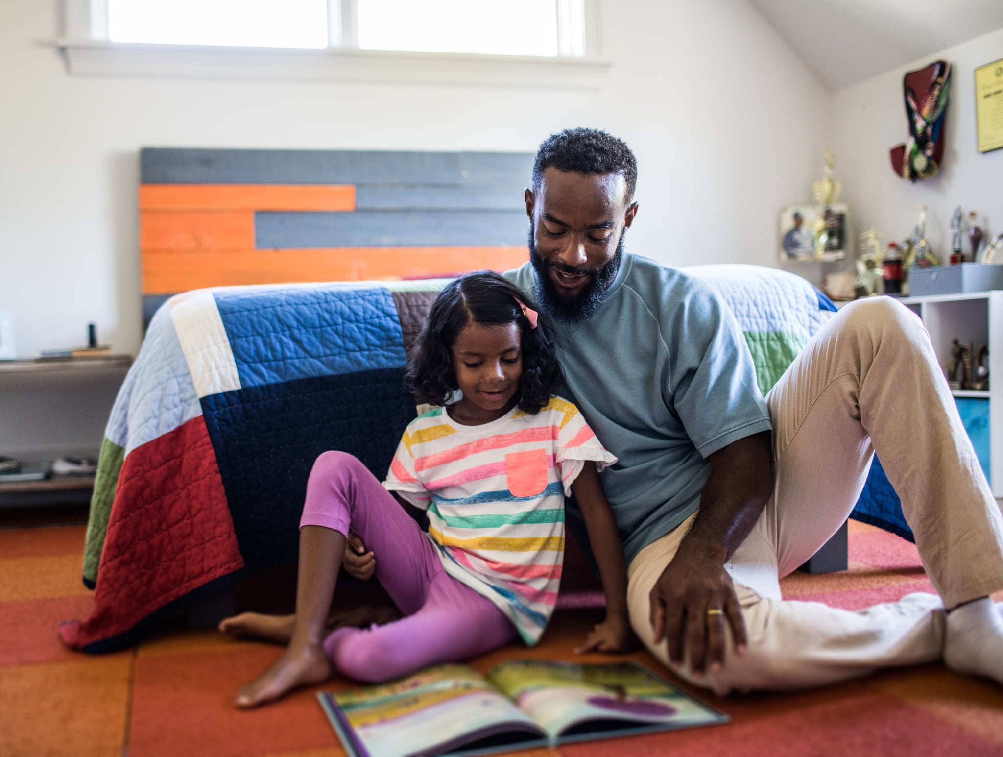 father and daughter reading in bedroom