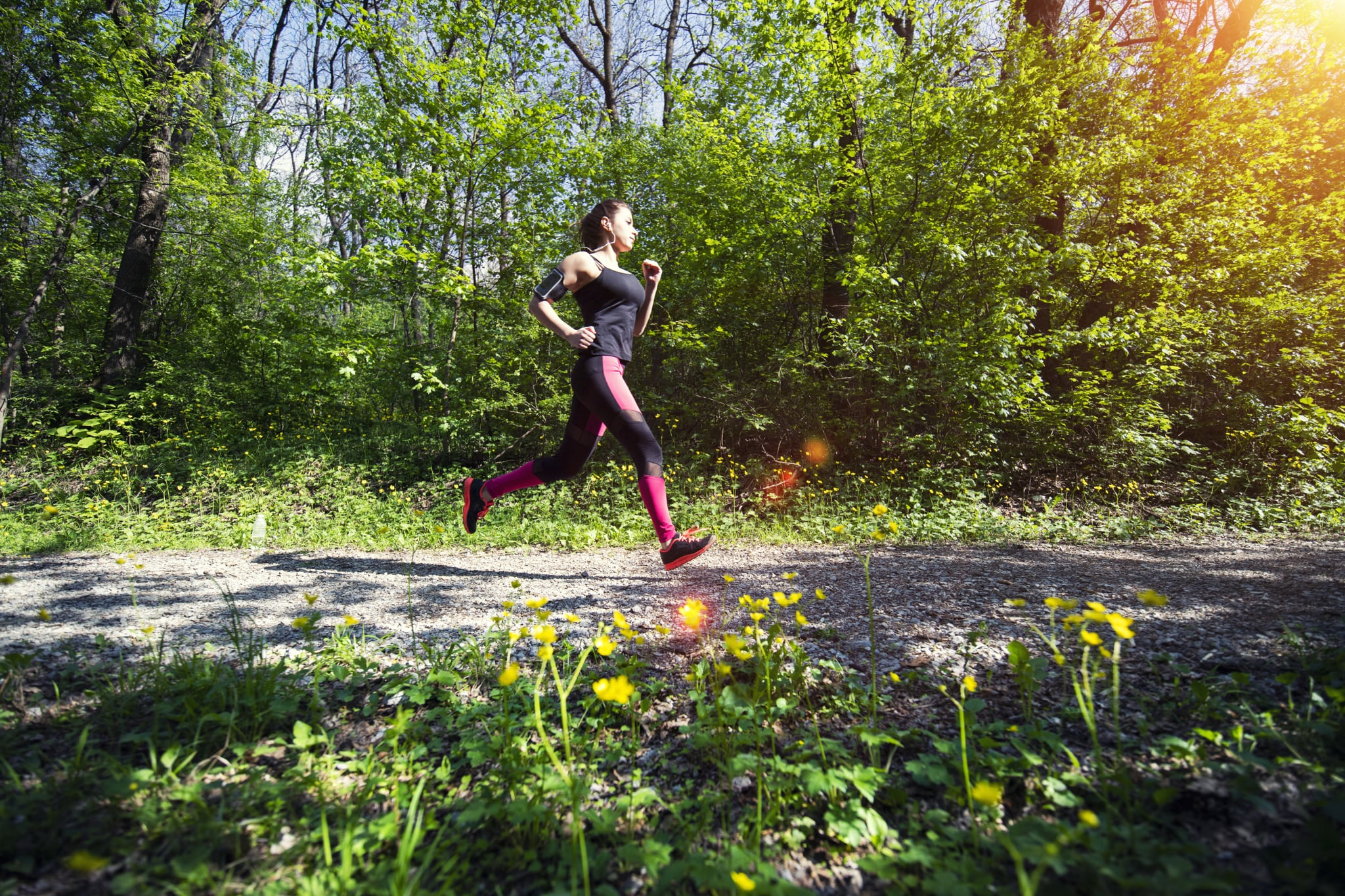 A young woman running in the forest footpath.