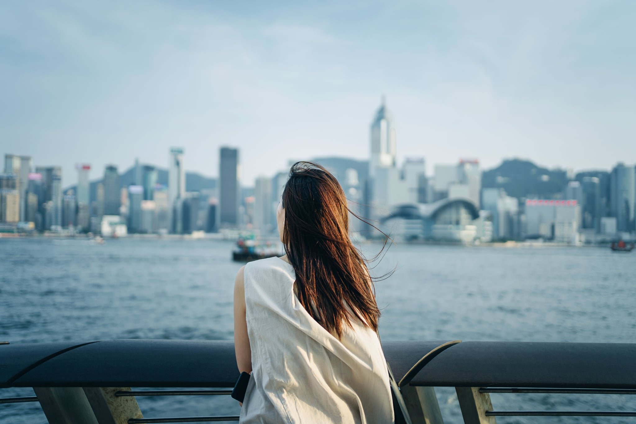 Relaxing young Asian woman traveller looking out over promenade of Victoria Harbour enjoying the gentle breeze and the beautiful cityscape at dusk