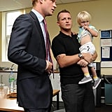 Prince Harry speaks with an ambulance crew member and his 2-year-old son, also named Harry.