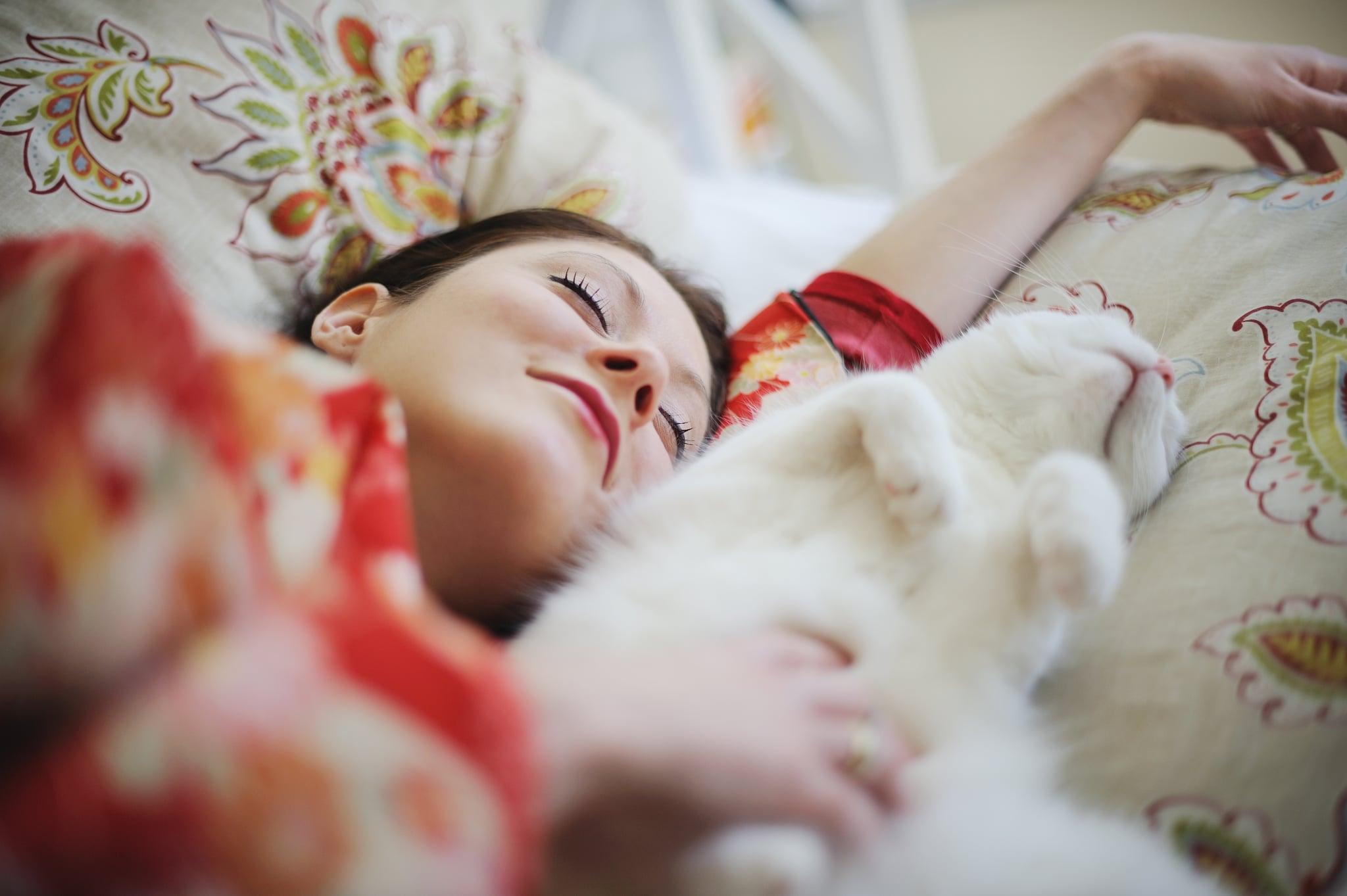 Smiling woman wearing  kimono, in bed, asleep next to white cat.